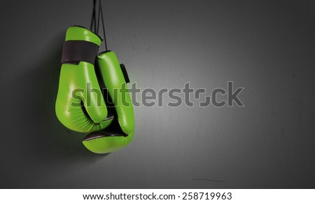 Pair of green boxing gloves hanging on all - stock photo