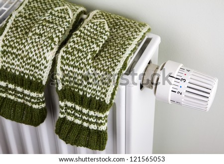 Pair of green knitted gloves drying on the radiator with thermostat - stock photo