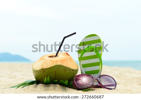 Pair of green striped sandal, sunglasses and coconut on the beach - stock photo