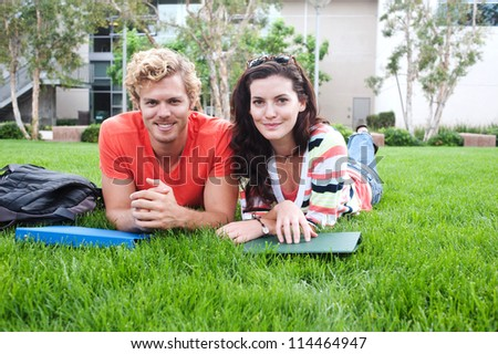 pair of happy college students lying in the grass - stock photo