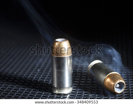 Pair of hollowpoint cartridges for a handgun with smoke - stock photo