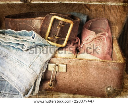 Pair of jeans, shoes, belt in a vintage suitcase - stock photo