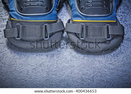 Pair of knee protectors on black background construction concept. - stock photo