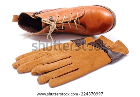 Pair of leather suede gloves for woman and overturned leather womanly shoes isolated on white background - stock photo