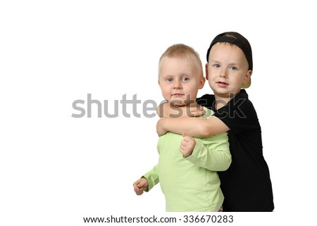 Pair of little children stand at full height embracing isolated on white background with copy space for text - friendship and togetherness - stock photo