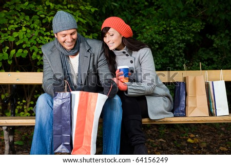 Pair of man and woman couple sitting on bank in park garden after shopping with bags - stock photo