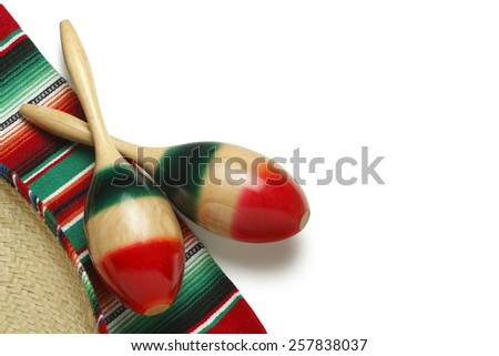 Pair of maracas and a sombrero on a colorful Mexican blanket on a white background - stock photo