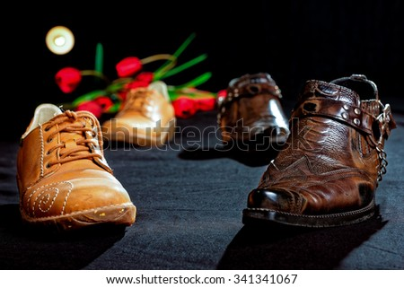 Pair of men shoes and pair of women shoes standing on the floor in the background of the tulips. - stock photo