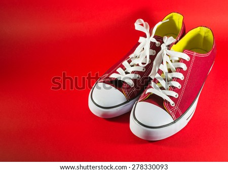 Pair of new red canvas trainers on a dark-red background - stock photo