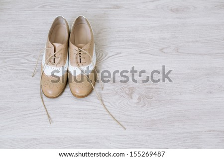 Pair of new unlaced womans shoes on a white wooden floor  - stock photo