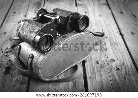 Pair of old binoculars with vintage leather strap and case on a rough wooden surface filtered in black and white - stock photo