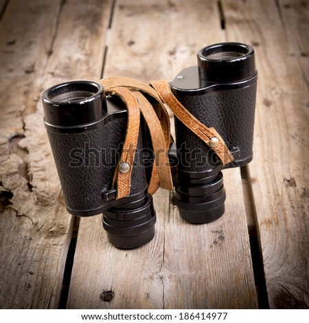 Pair of old binoculars with vintage leather strap on a rough wooden surface - stock photo