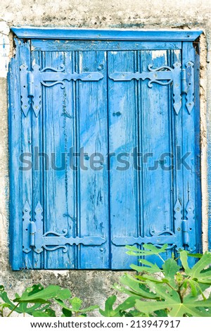 Pair of old blue wooden window shutters on a house in Greece - stock photo