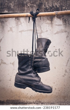 pair of  old boot hang on bamboo, process color - stock photo