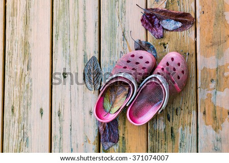 Pair of old dirty red garden shoes  on wooden deck floor. - stock photo