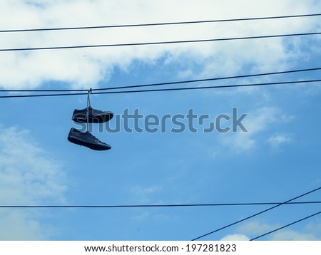 Pair of old sneakers hanging by their laces on a telephone wire - stock photo