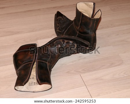 Pair of old worn brown western boots on wooden floor - stock photo