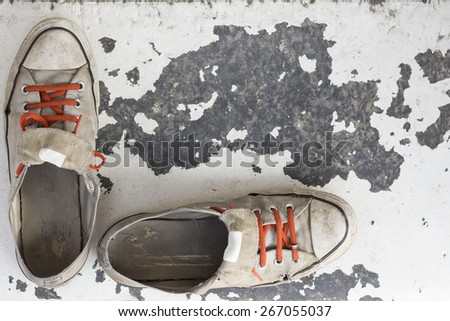 Pair of old worn classic sneakers for travel or point of view background - stock photo
