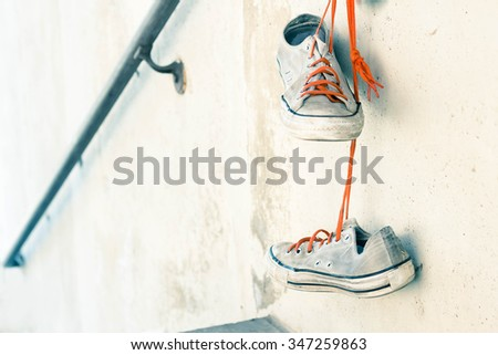 Pair of old worn classic sneakers hanging from railing - stock photo
