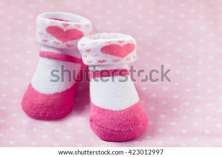 Pair of pink child socks closeup on spotted pink background, selective focus - stock photo