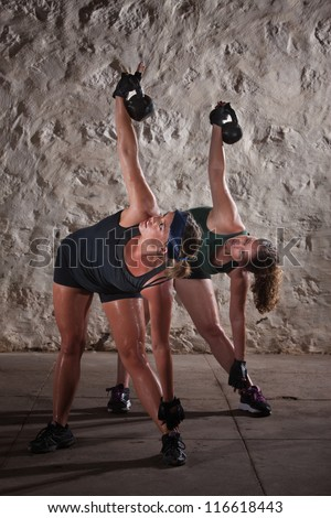 Pair of pretty women lifting kettlebell weights over their shoulders - stock photo