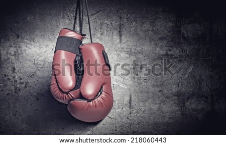 Pair of red boxing gloves hanging on wall - stock photo
