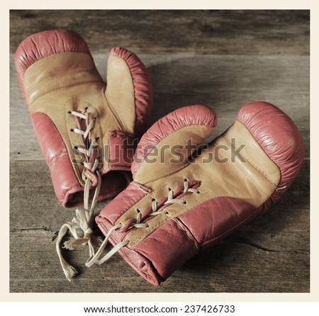 Pair of red boxing gloves on a table.  Cross processed to look like and instant picture. - stock photo