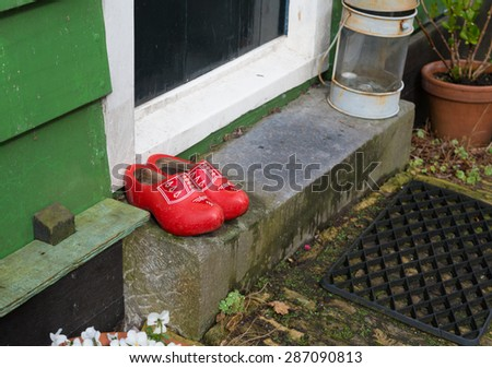 pair of red wooden shoes in front of a doorstep - stock photo