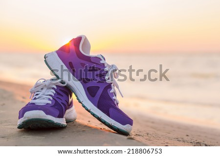 Pair of running shoes on the beach at sunset - stock photo