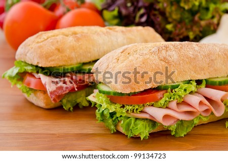 Pair of sandwiches filled with salami, chicken breast and lettuce - stock photo
