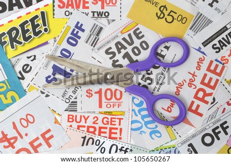 pair of scissors on grocery coupons - stock photo