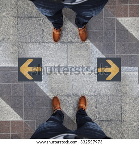 Pair of shoes standing with two yellow arrow - stock photo
