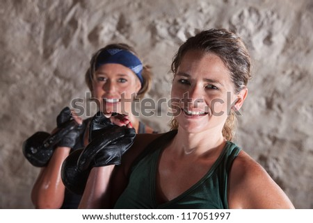 Pair of smiling ladies holding kettlebell weights - stock photo