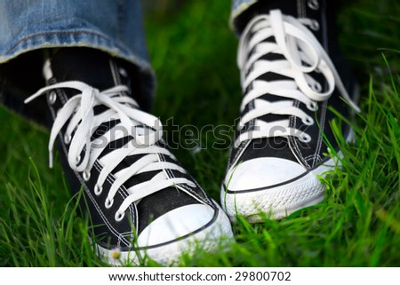 pair of sneakers in green grass - stock photo