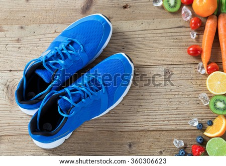 Pair of sport fitness shoes and fresh vegetables and fruits on wooden background, fitness background. - stock photo