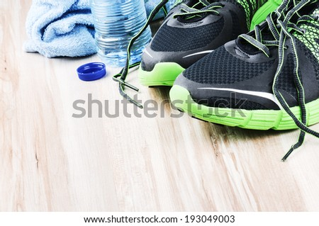 Pair of sport shoes and water bottle. After workout setting  - stock photo