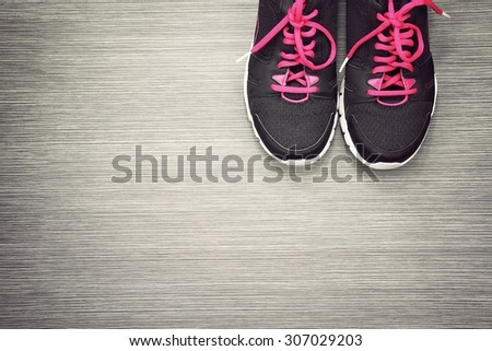 Pair of sport shoes on grey wooden background, Sport wear, Sport fashion, Sport accessories, Sport equipment. (Vintage Style Color) - stock photo