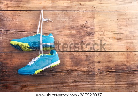 Pair of sports shoes hang on a nail on a wooden fence background - stock photo