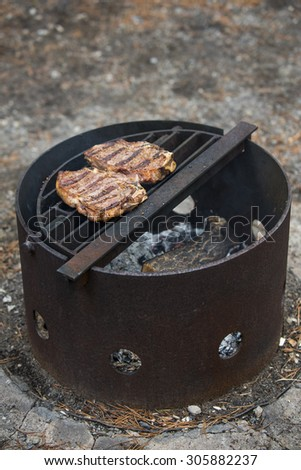 Pair of steaks grilling over a campfire - stock photo