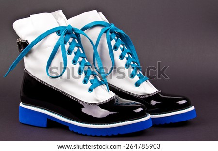 pair of stylish women's black and white shoes with blue laces and soles, on a gray background - stock photo