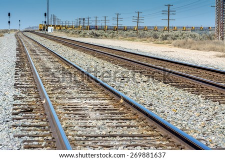 Pair of train tracks lead into the distance - stock photo