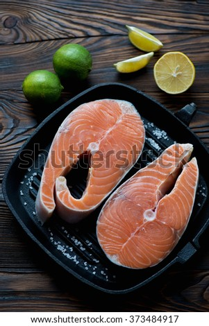Pair of uncooked salmon steaks with seasonings, above view - stock photo
