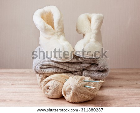 Pair of warm winter sheepskin slippers (alpaca), wool yarn , knitting needle ,  pile of warm woolen clothes (Selective focus) - stock photo
