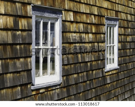 Pair of weathered windows in exterior wall of cedar shakes - stock photo