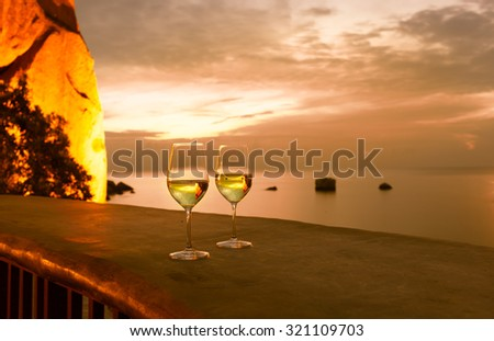 Pair of wine glasses in a beautiful sunset setting.  - stock photo