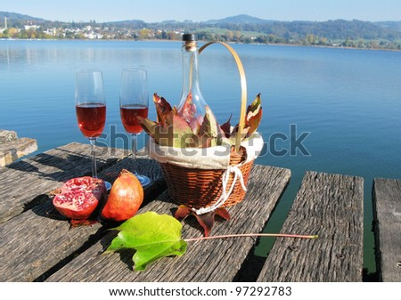 Pair of wineglasses, pomegranate and autumn leaves against a lake - stock photo