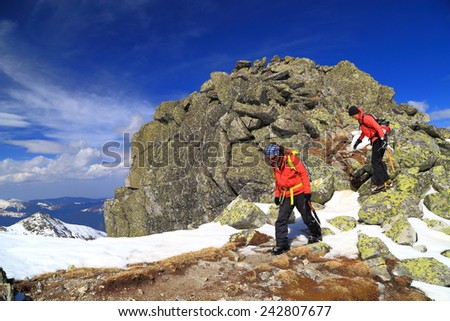 Pair of winter mountaineers crossing a rocky area on the mountain  - stock photo