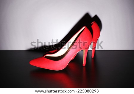 Pair of woman's red shoes on floor on light wall background - stock photo