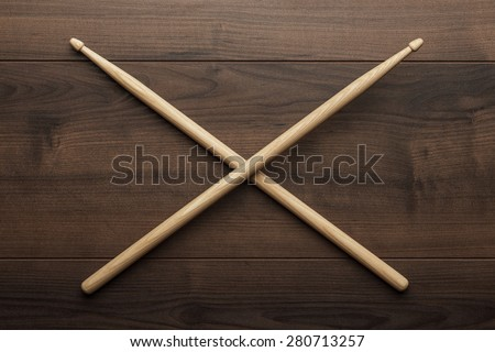 pair of wooden drumsticks crossed on wooden table - stock photo