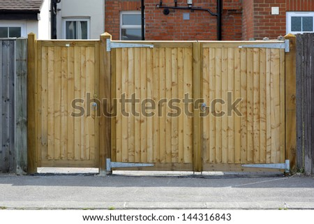 Pair of wooden gates for car access to house and separate side pedestrian access door - stock photo
